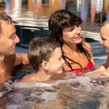 family-with-two-kids-enjoying-their-day-swimming-pool