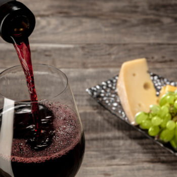 bottle-glass-red-wine-with-fruits-wooden-table